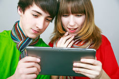 Boy and girl enjoying  tablet. Boy and girl enjoying new tablet Royalty Free Stock Photo
