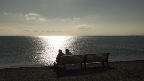 Boy and girl enjoying a view of the ocean on the coast at sunset.  stock video footage