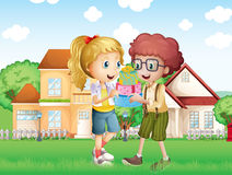 A boy and a girl exchanging gifts in front of the village Royalty Free Stock Photo
