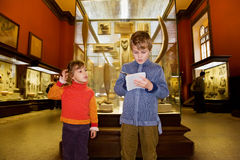 Boy and girl at excursion in historical museum. Boy and little girl at excursion in historical museum near exhibits of ancient relics in glass cases, boy writes Stock Image