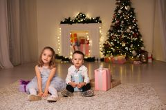 Boy and girl family opens Christmas gift new year holiday lights Christmas tree garlands stock images