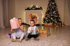 Boy and girl family opens Christmas gift new year holiday lights Christmas tree garlands stock photography