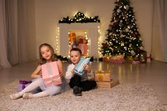 Boy and girl family opens Christmas gift new year holiday lights Christmas tree garlands stock image