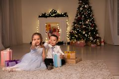Boy and girl family opens Christmas gift new year holiday lights Christmas tree garlands royalty free stock image