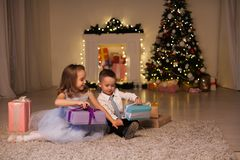 Boy and girl family opens Christmas gift new year holiday lights Christmas tree garlands royalty free stock images
