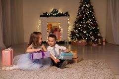 Boy and girl family opens Christmas gift new year holiday lights Christmas tree garlands stock photo