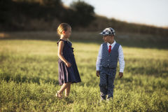 A boy and a girl in the field in the sunset light. Cute elegantly dressed boy and girl looking on each other in the field with a soft sunset light Royalty Free Stock Image