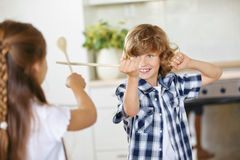 Boy and girl fighting in fun with spoons Stock Photography