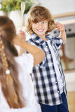 Boy and girl fighting in jest in kitchen Royalty Free Stock Image
