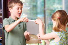 Boy And Girl Fighting Over Digital Tablet At Home royalty free stock images