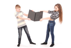 Boy and girl fighting over a laptop. Isolated on white royalty free stock photos