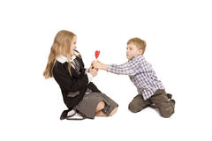 Boy and girl fighting over a lolipop. (isolated on white Stock Images