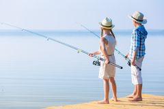 Boy and girl with fishing rods stock photos