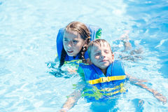 Boy and girl floating in water with life vest Stock Image