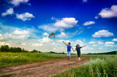Boy and girl flying a kite in a field Stock Image