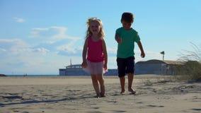 Boy and girl fool on the beach. Beautiful little boy and girl fool on the beach stock footage