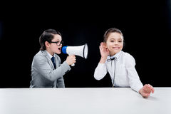 Boy and girl in formal wear interacting with bullhorn Royalty Free Stock Image