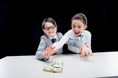 Boy and girl in formal wear reaching for money Royalty Free Stock Photo
