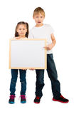 Boy and a Girl and a Frame with Copyspace. Boy and a girl hold a wooden frame with an empty copyspace, isolated royalty free stock photos