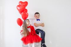Boy and girl friends with red balloons on Valentine`s Day holiday