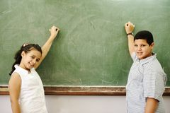 Boy and girl in front of board Stock Photography