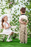 Boy and girl in the gazebo on the bench in the gar Royalty Free Stock Image