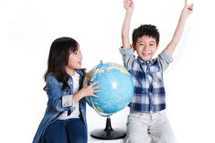 Boy and girl with a globe Royalty Free Stock Photos