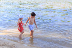 Boy and girl go in the cold water. Brother and sister walk by the river Stock Images