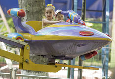Boy and girl go for a drive on the carousel. Rostov-on-Don, Russia- May 29,2016: Boy and girl with admiration go for a drive on the carousel in the park named Royalty Free Stock Image