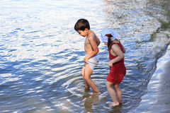 Boy and girl go in the water. Brother and sister walking on the beach royalty free stock photos