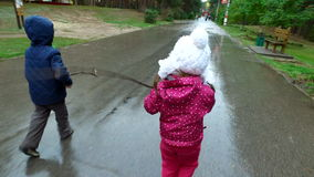Boy and girl go on a wet road. Children run through the puddles. Rain ended recently. Kids in autumn park stock footage