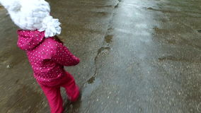 Boy and girl go on a wet road. Children run through the puddles. Rain ended recently. Kids in autumn park stock video footage