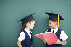 boy and girl in graduation cap and studying Royalty Free Stock Image