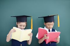 boy and girl in graduation cap and studying Royalty Free Stock Photo