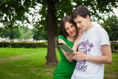 Boy and girl in green dress holding ipad together. Outdoor in the park Royalty Free Stock Images