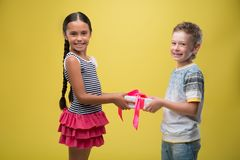 Boy and girl. Half-length portrait of lovely little smiling girl wearing nice striped dress and fair-haired nice boy standing aside taking a present from each Stock Images