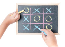 Boy and girl hand drawing a game of tic tac toe royalty free stock photo
