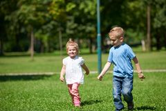 Boy and girl have fun and running in park Stock Photos