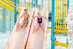 Boy and girl have fun in the water park.  Stock Photos