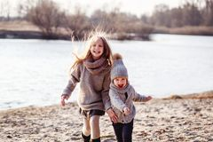 A boy and a girl having fun outside in early spring in the forest near the water. A sister and brothe together. stock photo