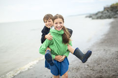 Boy and girl having fun on rain close to a sea. A boy and girl having fun on rain close to a sea royalty free stock images