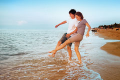 Boy and girl having fun sprinkled sea waves Royalty Free Stock Photography
