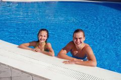 Boy and girl having fun in swimming pool Royalty Free Stock Images
