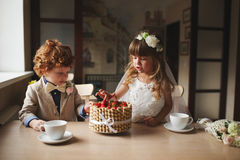 Boy and girl having tea party in cafe stock photo
