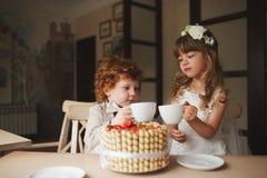 Boy and girl having tea party in cafe stock photos