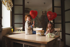 Boy and girl having tea party in cafe stock photography