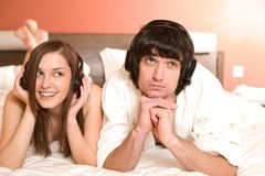 Boy and girl in headphones on bed Stock Image