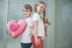 Boy and girl with heart shape cushion and teddy bear holding hands while standing back to back Royalty Free Stock Photography