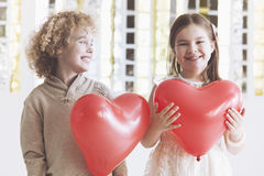 Boy and girl with hearts. Small boy and girl holding red balloon hearts Royalty Free Stock Image