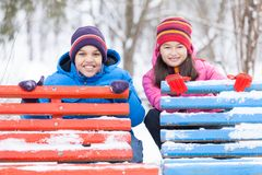 Boy and girl hiding behind benches. Stock Photo